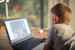 A young boy watching a movie on a laptop screen - restricting screen time