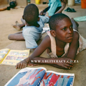 An African boy is lying on the ground with a friend reading.
