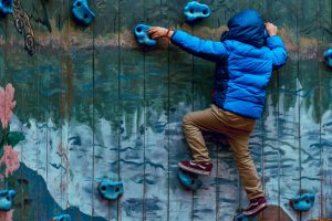 A boy climbing up a climbing wall.