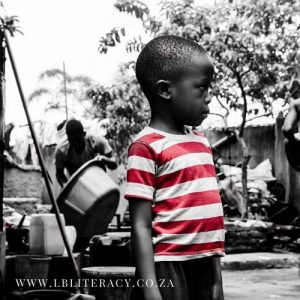 A young black child stands in the yard looking pensively towards his left while an older man does chores in the background. The only part of the picture that is in colour is the child's red and white t-shirt.