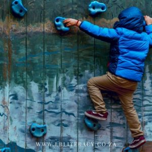 A boy is climbing a climbing wall using hand a foot holds.