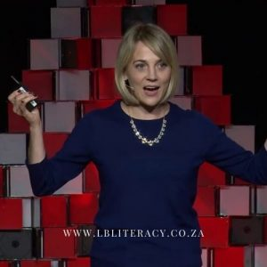 Rebecca Bellingham, dressed in a blue dress, addresses her audience.