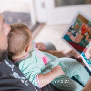 Dad reads a story to a baby to improve literacy.