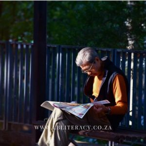 Old man reading a newspaper while sitting in a park.