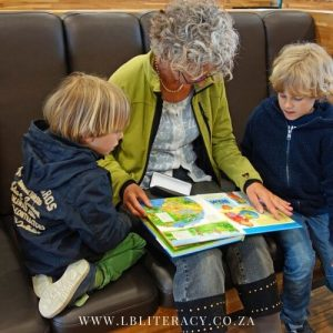 A Grandmother reads to her two grandchildren.